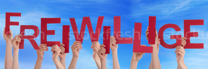 People Holding Red German Word Freiwillige Means Volunteer Blue  Stock photo © Nelosa