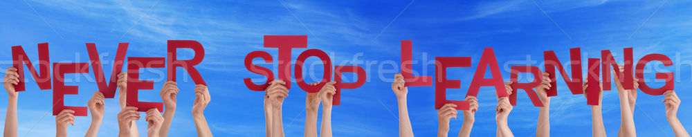 People Hands Holding Red Word Never Stop Learning Blue Sky Stock photo © Nelosa