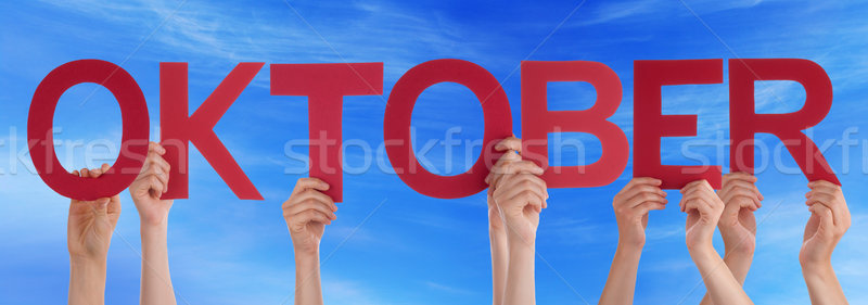 People Holding Straight German Word Oktober Means October Blue S Stock photo © Nelosa