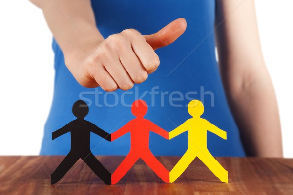 hand holding thumb up at paper chain people Stock photo © Nelosa