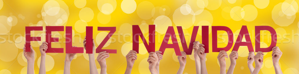 People Holding Feliz Navidad with Golden Background Stock photo © Nelosa