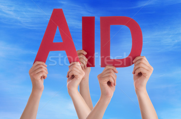 Stock photo: Many People Hands Holding Red Straight Word Aid Blue Sky