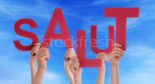 People Holding French Word Salut Means Hello Blue Sky Stock photo © Nelosa