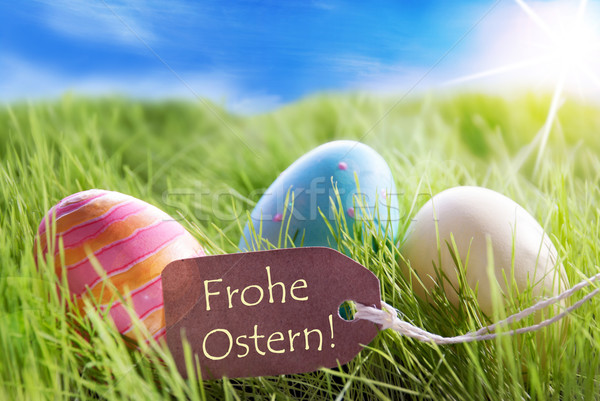 Three Colorful Easter Eggs On Sunny Green Grass With Label With German Frohe Ostern Means Happy East Stock photo © Nelosa