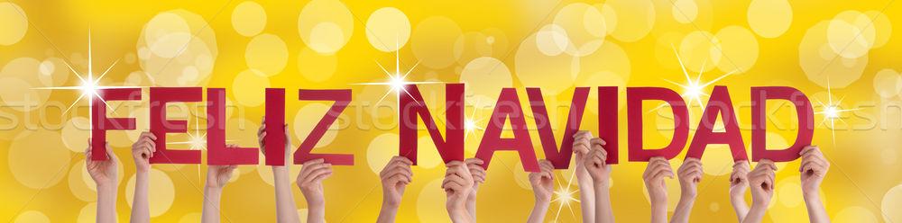 Hands Holding Feliz Navidad with Golden Background Stock photo © Nelosa
