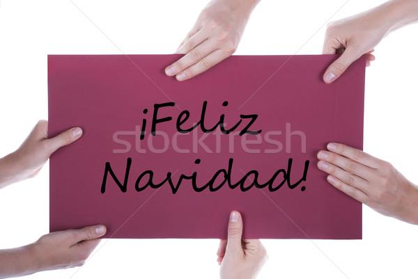 Hands Holding Sign with Feliz Navidad Stock photo © Nelosa