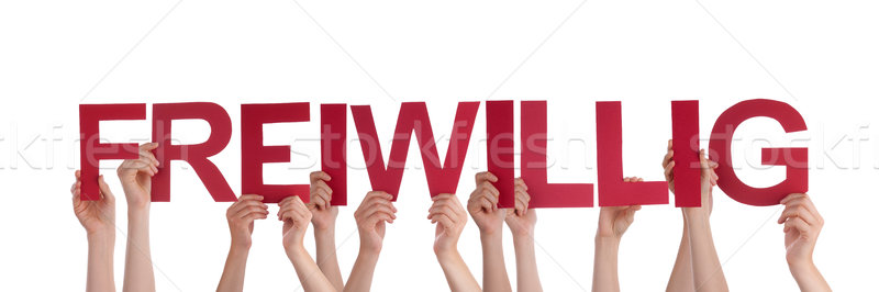 People Holding Red Straight German Word Freiwillig Means Volunta Stock photo © Nelosa