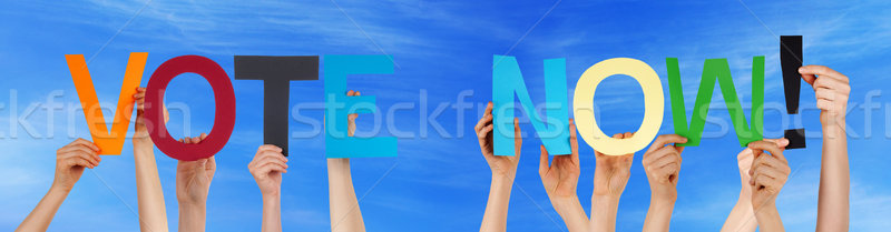 People Hands Holding Colorful Straight Word Vote Now Blue Sky Stock photo © Nelosa