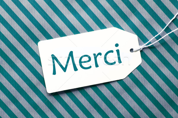Label On Turquoise Wrapping Paper, Merci Means Thank You Stock photo © Nelosa