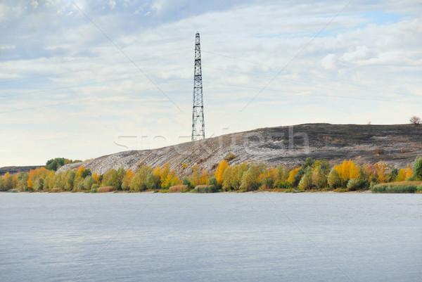 High voltage line and electricity pylon on coastline of river. Stock photo © nemalo