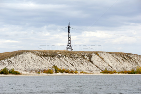 High voltage line and electricity pylon on coastline of river. Stock photo © nemalo