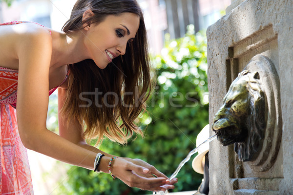 Beautiful woman drinks water from source in summer city park.  Stock photo © nenetus