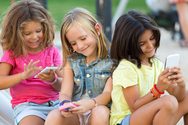 Group of childrens chatting with smart phones in the park. Stock photo © nenetus