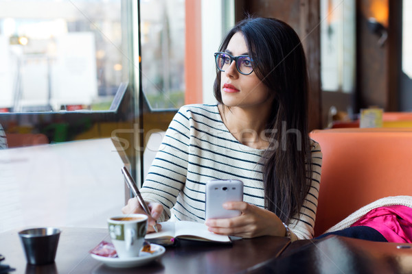 Young beautiful woman using her mobile phone in coffee. Stock photo © nenetus