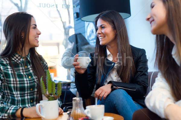 Three young woman drinking coffee and speaking at cafe shop. Stock photo © nenetus