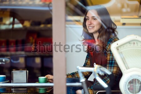 Beautiful young woman drinking coffee in cafe shop. Stock photo © nenetus