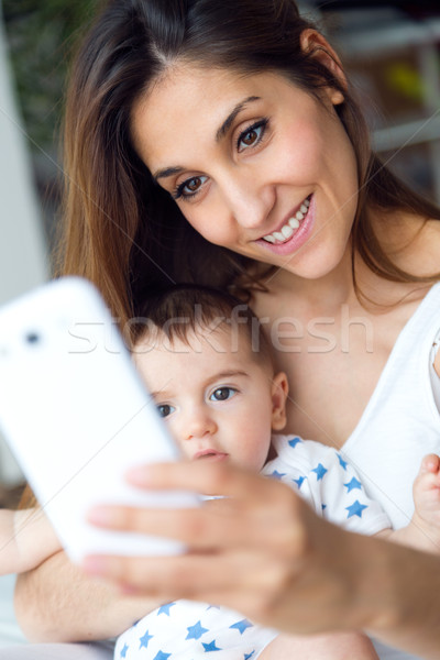 Beautiful mother and baby taking a selfie at home. Stock photo © nenetus