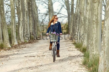 Pretty young girl riding bike and listening to music. Stock photo © nenetus
