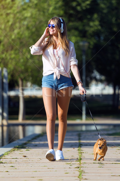 Beautiful young woman walking with her dog in the park. Stock photo © nenetus