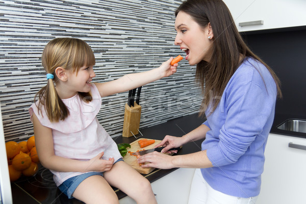 Jonge vrouw meisje eten wortelen keuken portret Stockfoto © nenetus