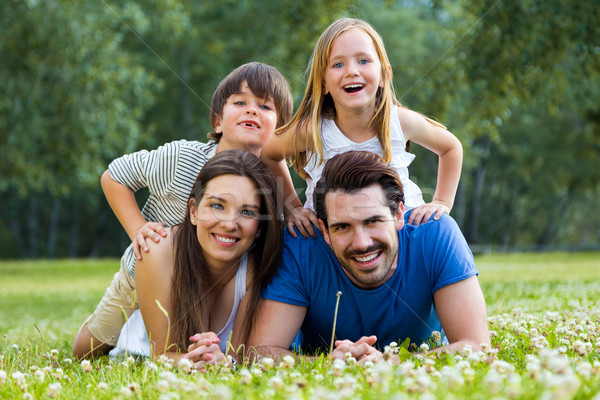 Happy young Family lying on grass  Stock photo © nenetus