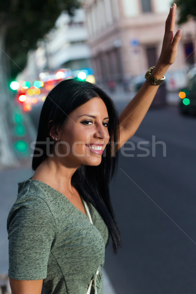 Young girl calling a taxi in the city at night. Stock photo © nenetus