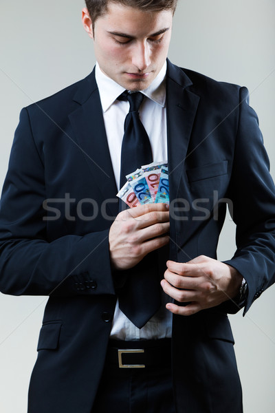 Young man in formalwear putting money in his pocket. Stock photo © nenetus