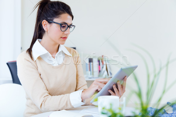 Young businesswomen working with digital tablet in her office. Stock photo © nenetus