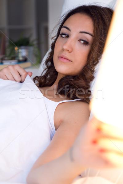 Beautiful young woman turning off the lamp. Stock photo © nenetus