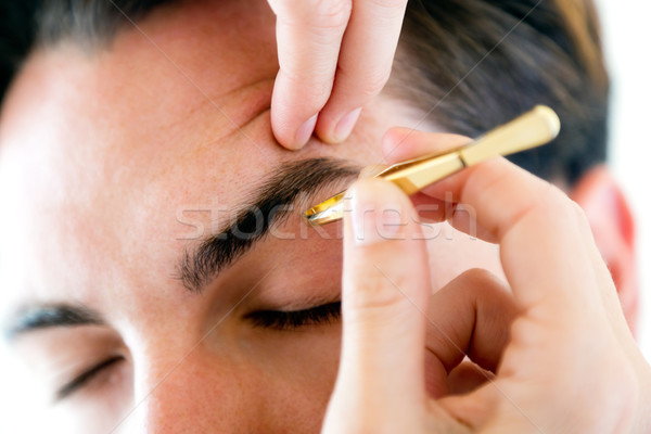 Man removing eyebrow hairs with tweezing. Stock photo © nenetus