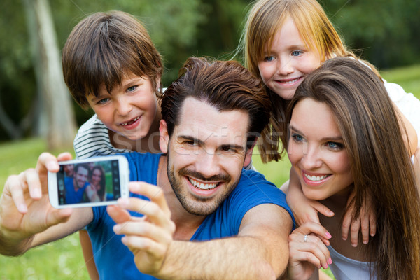 Happy young family taking selfies with her smartphone in the par Stock photo © nenetus