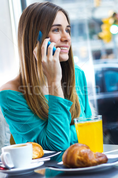 Cute brunette woman in cafe is speaking by mobile phone Stock photo © nenetus