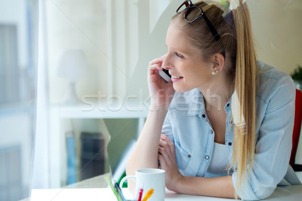 Young beautiful woman using her mobile phone at home. Stock photo © nenetus