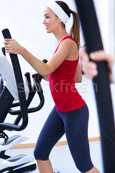 Happy young woman  with elliptic machine in the gym Stock photo © nenetus