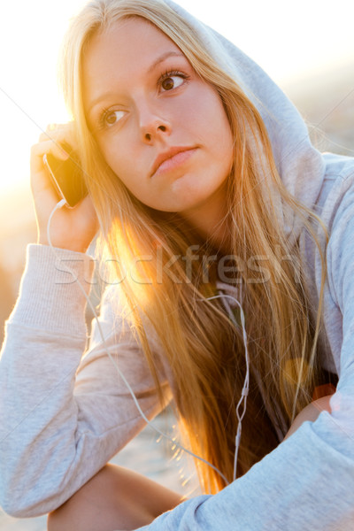 Stock photo: Beautiful girl sitting on the roof and listening to music.