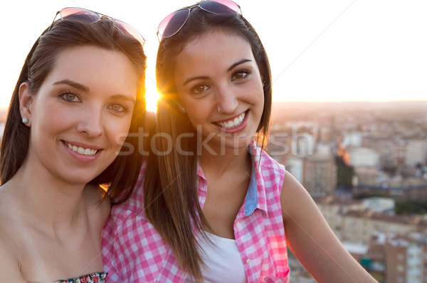 Pretty girls sitting on the roof at sunset. Stock photo © nenetus