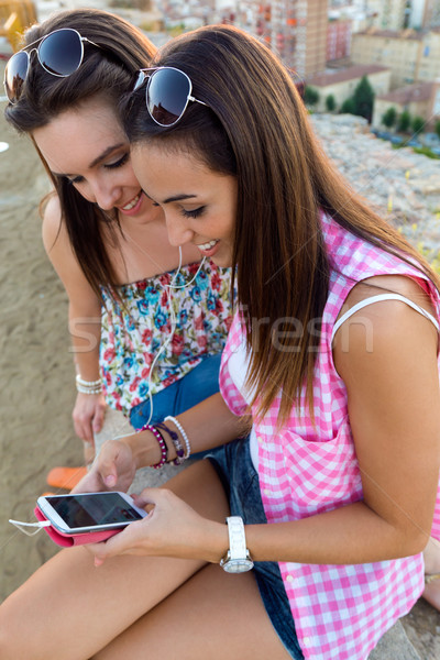 Stock photo: Beautiful girls sitting on the roof and listening to music at su