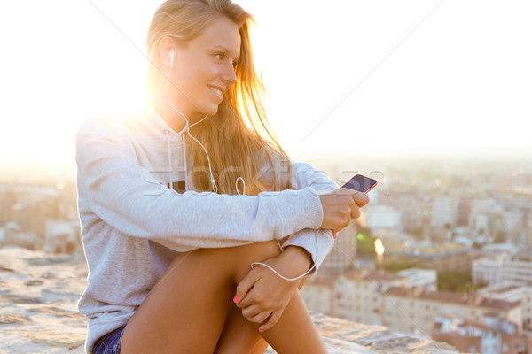 Beautiful girl sitting on the roof and listening to music. Stock photo © nenetus