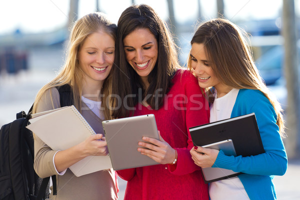 Students having fun with smartphones and tablets after class Stock photo © nenetus