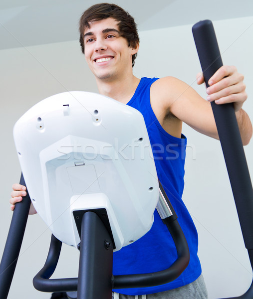 Happy young man with elliptic machine in the gym Stock photo © nenetus