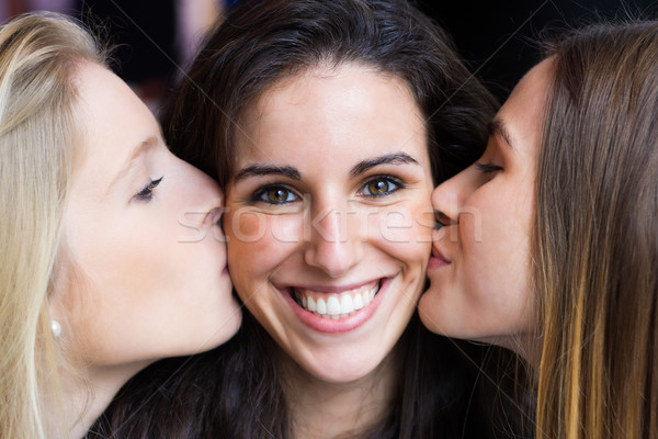 Cute smiling girl kissed on the cheeks by her friends. Stock photo © nenetus