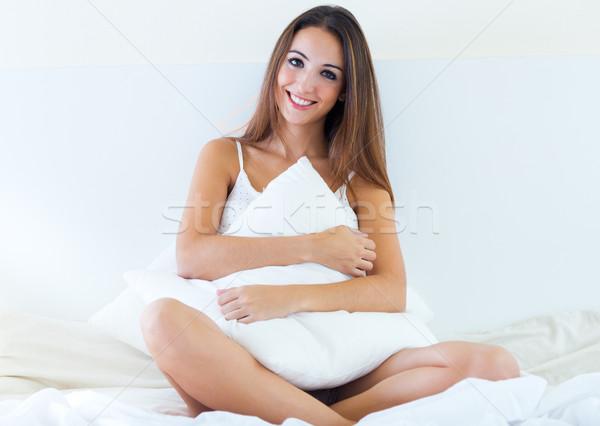 Mooie jonge vrouw vergadering bed geïsoleerd witte Stockfoto © nenetus