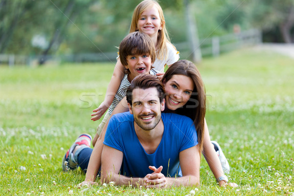 Stock photo: Happy young Family lying on grass
