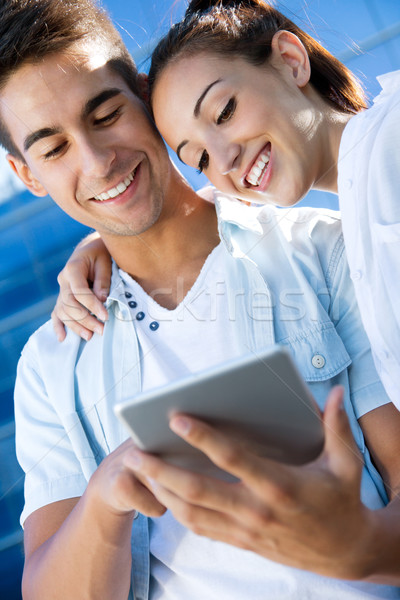 Outdoor portrait of one young couple using a digital tablet Stock photo © nenetus