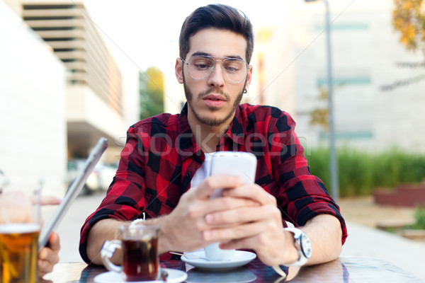 Young entrepreneur using his mobile phone at coffee shop.  Stock photo © nenetus