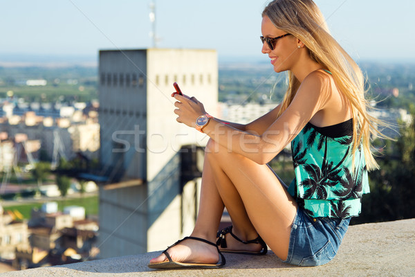 Beautiful blonde girl sitting on the roof with mobile phone. Stock photo © nenetus