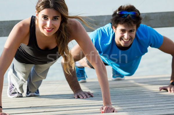 Couple doing push ups near the sea Stock photo © nenetus