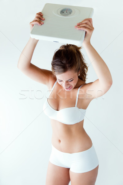 Frustrated woman with scale. Isolated on white. Stock photo © nenetus