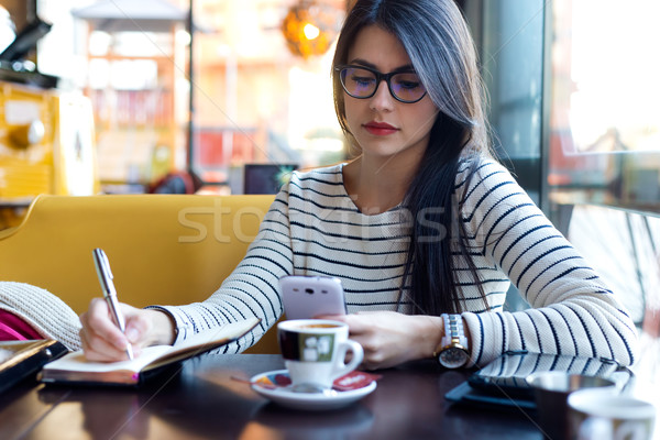 Stock photo: Young beautiful woman using her mobile phone in coffee.