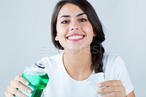 Beautiful girl using mouthwash. Isolated on white. Stock photo © nenetus